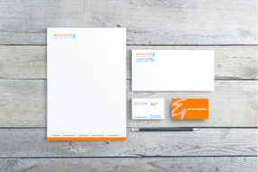 Image of letterhead, envelope and business cards with a Moulton & Associates logo in orange laying on a gray wood background.